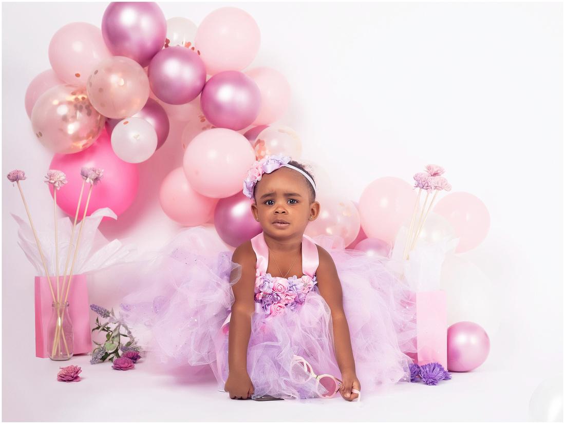 Kiara's 2nd Birthday Shoot in studio in Bridgeport, CT. Purple and pink theme with balloon garland. Birthday photo shoot ideas for toddler girls.